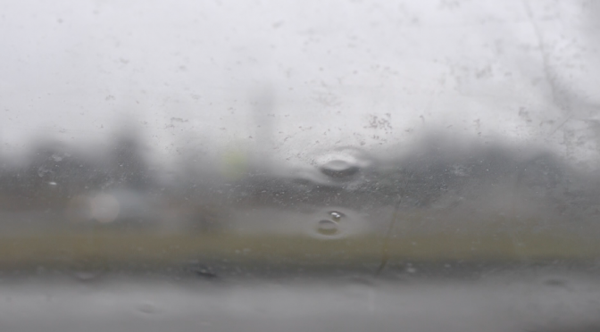 Rainy day. View through the car window. Focus on the window