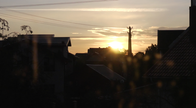 Sun goes up above the roofs of houses. Free timelapse video footage