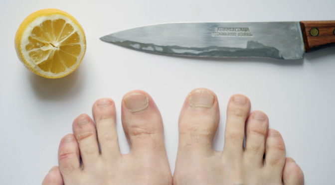 Composition with lemon, knife and man's foot. Free HD video footage