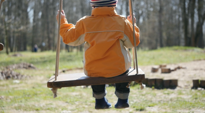 A boy is swinging in a playground. Free HD video footage