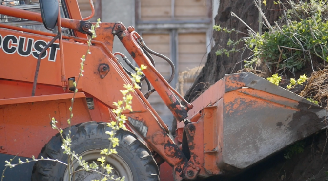 A mini excavator is digging a mound of soil. Free HD video footage