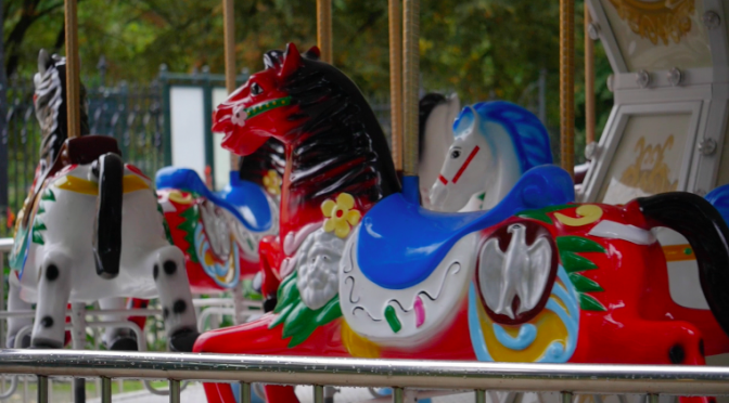 Rotating carousel with the wooden horses on a platform. Free HD video footage