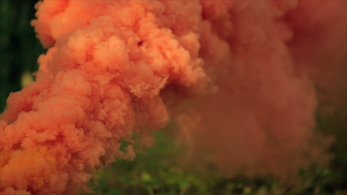 Orange smoke grenade in slow motion. Free HD video footage